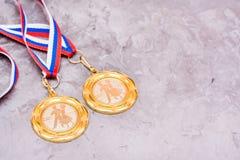 在一卷磁带上的两枚奖牌在灰色背景 免版税库存图片