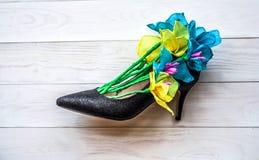 在一双夫人鞋子的春天纸花在白色木背景 开花礼物在一妇女` s天 免版税库存照片