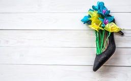 在一双夫人鞋子的春天纸花在白色木背景 开花礼物在一妇女` s天 免版税图库摄影