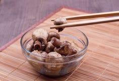 在筷子的油煎的蘑菇 免版税库存图片