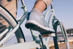 在一双蓝色运动鞋和一辆自行车的女性脚在海滩 库存照片