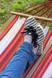在一双镶边吊床、佩带的牛仔裤和布料鞋子的盘的腿 免版税库存照片