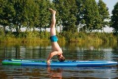 在一口板的瑜伽,在水的锻炼, 免版税库存图片
