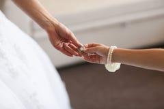 在一只女性手上的婚姻的耳环,她采取耳环,费早晨新娘,白色礼服 免版税库存照片