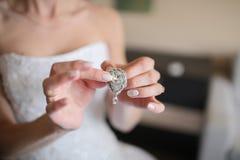 在一只女性手上的婚姻的耳环,她采取耳环,费早晨新娘,白色礼服 免版税库存图片