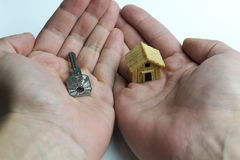 在一只手上另一个房子的一把钥匙 免版税库存图片