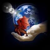 在一只手上的红色龙在地球的背景 库存照片