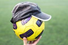 在一只手上的足球在盖帽 图库摄影
