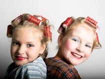 在一只眼睛前面的两个嬉戏的十几岁的女孩愉快地笑在照相机的,他们肩并肩站立 图库摄影