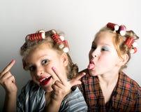 在一只眼睛前面的两个嬉戏的十几岁的女孩 库存照片