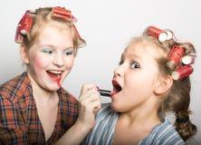 在一只眼睛前面的两个嬉戏的十几岁的女孩 库存图片