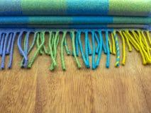 在一只笼子的羊毛围巾在一张木桌上的蓝色和绿色树荫下 库存图片