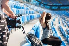 在一台专业照相机的videographer射击喜欢一运动女孩做准备,坐在体育场内 库存图片