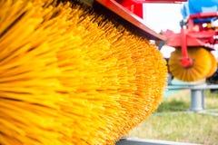 在一台拖拉机的一个机盖有一把转动的刷子的清除从路的雪,黄色堆 免版税库存照片