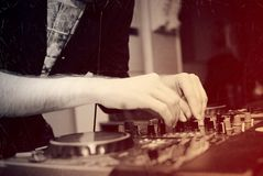 在一台搅拌器的DJ混合的轨道在夜总会 免版税库存图片