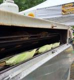在一台烘烤器的新鲜的玉米棒子在公平一条地方的街道 库存照片