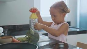 在一台磨丝器的逗人喜爱的小孩女孩摩擦红萝卜在国内厨房 股票录像