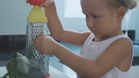 在一台磨丝器的逗人喜爱的小孩女孩摩擦红萝卜在国内厨房 影视素材