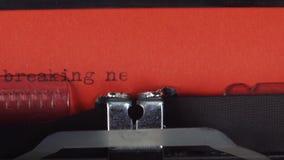 在一台老葡萄酒打字机-键入的最新新闻 打印在红色纸 红色纸被插入入打字机 影视素材