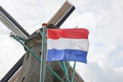 在一台老风车前面的荷兰旗子 免版税库存照片