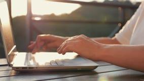 在一台膝上型计算机的妇女键入的文本在她的工作场所 日落的女孩在阳光下 电子网上购物 股票视频