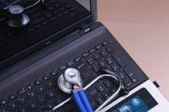 在一台膝上型计算机附近的一个医疗听诊器在一张木桌上 库存图片