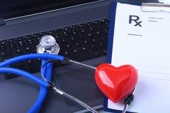在一台膝上型计算机附近的一个医疗听诊器有在一张木桌上的红色心脏的,在白色 免版税库存照片