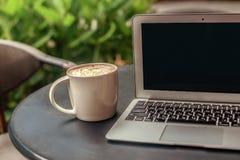 在一台膝上型计算机附近的大加奶咖啡杯子在绿色植物背景的一张书桌上 图库摄影