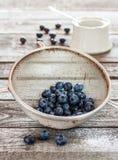 在一台金属过滤器的蓝莓在葡萄酒木头桌上 库存图片