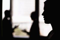 在一名女实业家的旁边外形有工友的在背景,剪影中 图库摄影