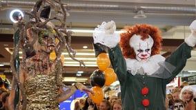在一名妇女旁边的邪恶的小丑立场在最佳的服装的比赛的一套Gorgon服装的为万圣夜 股票视频