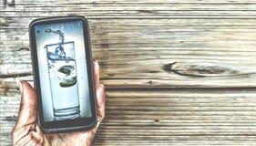 在一名妇女的一个智能手机有一杯的图片的在显示的净水 概念:健康生活方式,饮食,秀丽 免版税库存照片