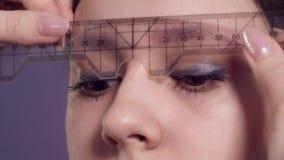 在一名妇女的眼眉的画的等高申请永久构成的在发廊 股票视频