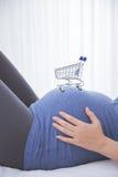 在一名孕妇,购物的概念的胃的一辆台车 库存照片