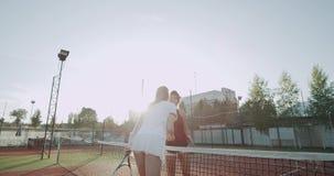 在一场坚硬网球比赛以后的两个美丽的朋友夫人,握手和亲吻,在网球场 影视素材