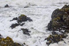 在一场强的冬天风暴期间,爱尔兰海的搅动的水作为波浪在岸打破 免版税库存图片
