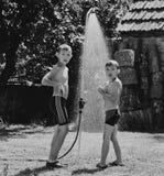 在一场阵雨下的男孩在庭院里 免版税图库摄影
