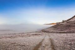 在一场雾的乡下公路在山 库存照片