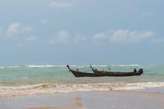 在一场风暴的小渔船在海滩附近 库存图片