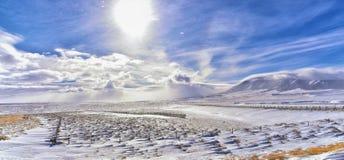 在一场飞雪期间的怀俄明乡下全景与与积雪的山与阴云密布灰色多云天空 免版税库存图片