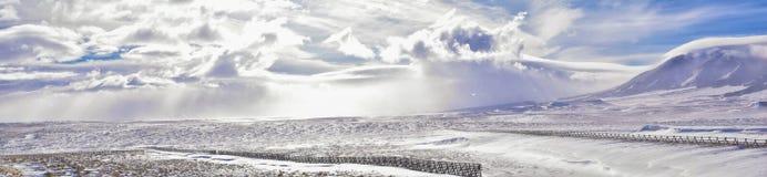 在一场飞雪期间的怀俄明乡下全景与与积雪的山与阴云密布灰色多云天空 库存照片