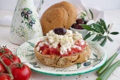在一块传统板材的Dakos传统希腊开胃菜有陶瓷橄榄油瓶子、干黑麦面包、橄榄和橄榄树枝的 库存图片