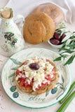 在一块传统板材的Dakos传统希腊开胃菜有陶瓷橄榄油瓶子、干黑麦面包、橄榄和橄榄树枝的 图库摄影