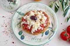 在一块传统板材的Dakos传统希腊开胃菜有陶瓷橄榄油瓶子、干黑麦面包、橄榄和橄榄树枝的 Healt 库存图片