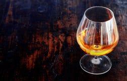 在一块典雅的一口威士忌酒玻璃的发光的科涅克白兰地 库存照片