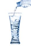 在一块典雅的高玻璃的倾吐的水与冰和水下落 免版税库存照片