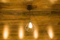 在一块古铜色棕色木天花板的现代时髦的几何灯 免版税库存照片