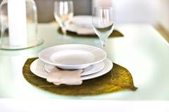 在一块叶子设计和玻璃的空的板材与桌设定 免版税库存照片