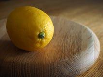 在一块圆的木砧板的柠檬 库存照片