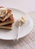 在一块圆的板材和一把匙子的乳酪蛋糕有奶油的 免版税图库摄影